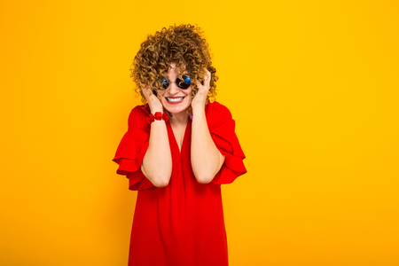 Portrait of a white woman with afrro curly hairstyle in red dress and sunglasses covering ears with hands doesn-t want to listen isolated on orange background with copyspace beauty salon concept. Stock Photo