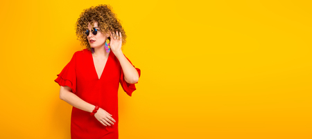 Portrait of a white woman with afrro curly hairstyle in red dress and sunglasses holding hand near her ear cant hear isolated on orange background with copyspace beauty salon advertising concept.