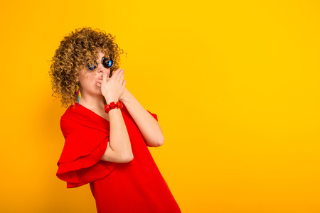 Portrait of a white woman with afrro curly hairstyle in red dress and sunglasses covering her mouth with hands in shock isolated on orange background with copyspace beauty salon advertising concept. Stock Photo