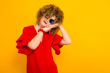 Portrait of a white woman with afrro curly hairstyle in red dress and sunglasses holding her face on palms isolated on orange background with copyspace beauty salon advertising concept.