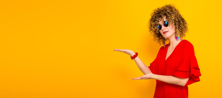 Portrait of a white woman with afrro curly hairstyle in red dress and sunglasses pointing with her hands at empty space with your text isolated on orange background with copyspace advertising concept.