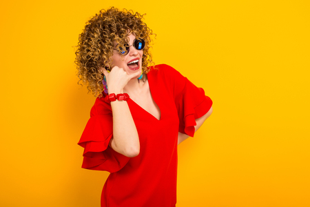Portrait of a white woman with afrro curly hairstyle in red dress and sunglasses making call gesture with her fingers isolated on orange background with copyspace. 写真素材