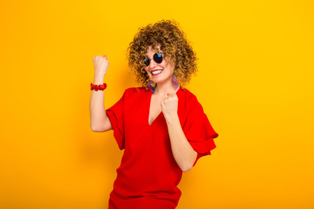 Portrait of a white cheerful woman with afrro curly hairstyle in red dress and sunglasses celebrating something with fists up isolated on orange background with copyspace winning concept.