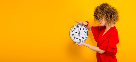 Portrait of a white woman with afrro hairstyle in red dress and sunglasses holding watches isolated on orange background with copyspace punctuality being on time or late concept horizontal picture.