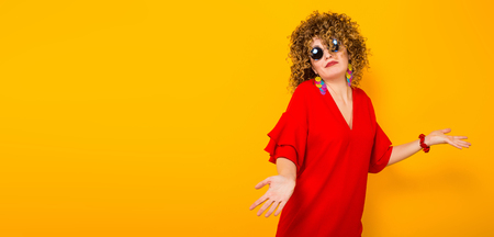 Portrait of a white woman with afrro curly hairstyle in red dress and sunglasses holds hands spread doesnt know what to do isolated on orange background with copyspace horizontal picture.