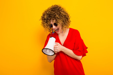 Portrait of a white woman with afrro curly hairstyle in red dress and sunglasses shouting into megaphone isolated on orange background with copyspace making announcement concept.
