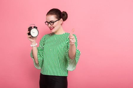 Portrait of attractive businesswoman with hair bun in striped blouse and eyeglasses showing alarm clock and thumb up isolated on pink background with copyspace punctuality being on time concept.