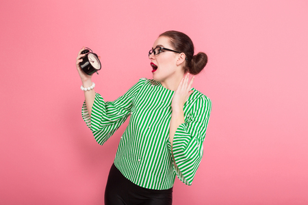 Portrait of attractive businesswoman with hair bun in striped blouse and eyeglasses looking at alarm clock in shock isolated on pink background with copyspace punctuality being late concept. Banque d'images