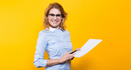 Portrait of attractive blonde businesswoman in blue shirt and eyeglasses isolated on orange backgroung holding blank paper list and pencil signing a contract agreement bargain concept. Standard-Bild
