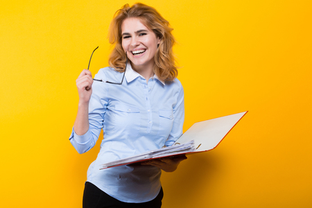 Portrait of attractive sexy businesswoman in blue shirt and glasses isolated on orange background checking readings in open big folder with files graduate or course work report presentation concept.