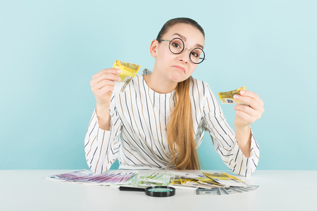 Portrait of attractive woman in striped shirt and eyeglasses isolated on blue background with magnifying glass counting euro banknotes checking if it is fake counterfeiter greed concept. Stock Photo