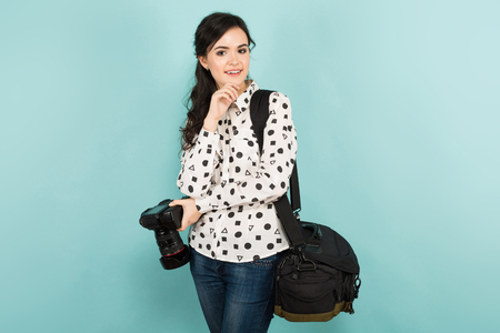 Portrait of young attractive woman photographer in white shirt holding camera and bag isolated on blue background with copyspace.