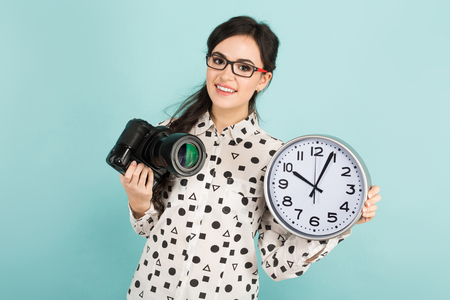 Portrait of young attractive woman photographer in white shirt and glasses holding camera and watches isolated on blue background with copyspace punctuality time is money concept.