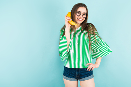 Portrait of attractive happy long-haired girl in striped shirt, glasses and jeans shorts holding banana like cellphone isolated on blue background with copyspace healthy way of life concept. Foto de archivo