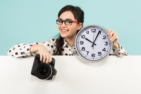 Portrait of young attractive woman photographer in white shirt and glasses holding camera and watches over white banner isolated on blue background with copyspace punctuality time is money concept. Banque d'images