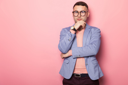 Portrait of handsome man in eyeglasses, pink jumper and blue jacket propping up his chin isolated on pink background with copyspace male fashion advertising concept.