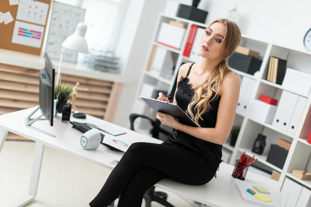 Beautiful young girl with blond hair in a black blouse is working in the office. photo with depth of field Stock Photo