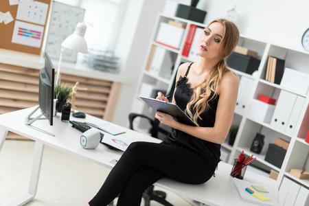 Belle jeune fille aux cheveux blonds dans un chemisier noir travaille au bureau. photo avec profondeur de champ