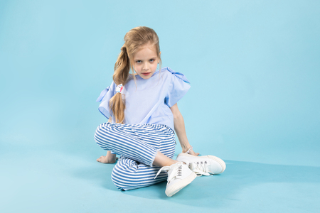 A teenage girl in a blue T-shirt, striped trousers and white sneakers is having fun on a light blue background.
