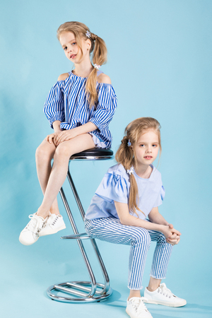 Girls teenagers in striped blue clothes and white sneakers posing on a light-blue background.