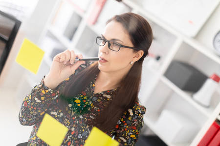A beautiful young girl with long dark hair works in a bright office. Girl in a ruffle shirt and glasses. photo with depth of field