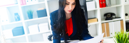 Portrait of a young girl in a suit. Beautiful girl is working in the office.