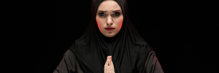 Attractive confident serious muslim arabian woman dressed in black hijab standing in studio looking away with arms near her face as religion faith concept