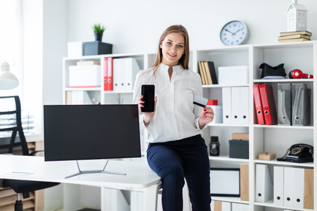 Slender young girl working in a bright office. Young girl in white blouse and black trousers. She has long brown hair. Girl with glasses and beautiful makeup. photo with depth of field