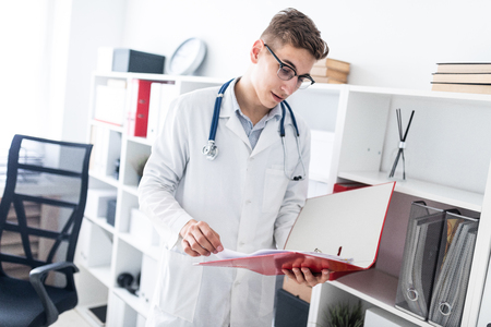 A handsome young man with dark hair in a white robe stands in a bright office and flips through a folder with documents. He has a phonendoscope around his neck. photo with depth of field
