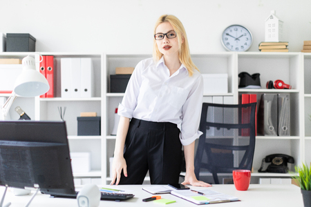 Beautiful young girl working in a bright office at a computer Desk. The girl has white hair and wearing glasses. Shes wearing a white shirt and black pants. photo with depth of field