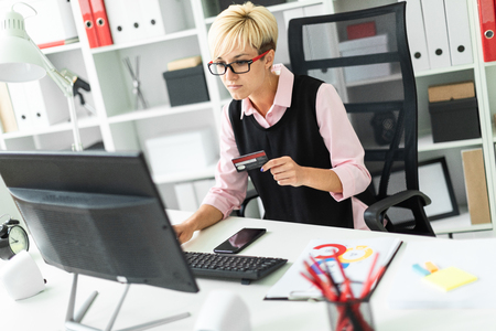 Beautiful young girl working in a bright office. She enters her credit card information into the computer. The girl has short white hair. Shes wearing a pink shirt and a black tank top. photo with depth of field