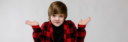 Portrait of small adorable confused stylish confident caucasian guy standing in studio looking in camera with open hands 免版税图像