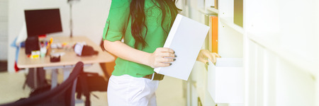 A beautiful girl in a green blouse and white trousers stands near the shelves with documents. photo with depth of field. Stock Photo