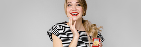 Portrait of beautiful caucasian friendly positive funny woman standing in studio looking in camera with red lips in bright clothes showing currency