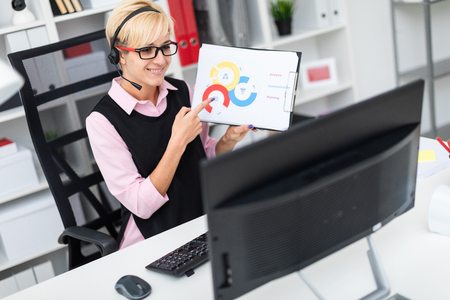 Beautiful young girl working in a bright office. The girl has short white hair. Shes wearing a pink shirt and a black tank top. photo with depth of field Banque d'images