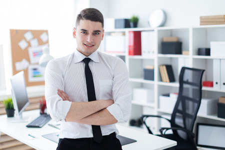 Charming young man working in a bright office. Young man in white shirt with black tie and black trousers. photo with depth of field