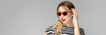 Portrait of woman with pony tail wearing stylish sunglasses, striped top and pants touching her hair isolated on grey background with copyspace fashion advertising or beauty salon concept.