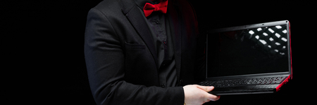 Young caucasian elegant successful smiling smart business man in black suit and red bow-tie standing in office looking in laptop Stock Photo