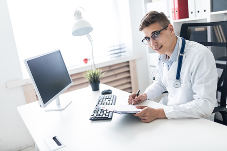 A handsome young man with dark hair in a white robe works at a computer Desk in a bright office. He has a phonendoscope around his neck. photo with depth of field