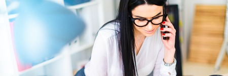 A young girl with glasses, wearing a white blouse and black trousers, works in the office. The girl has long straight black hair. photo with depth of field Stockfoto