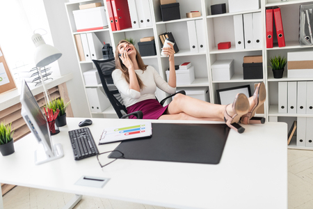Beautiful girl working in a bright office. Before the girl on the white table are documents. photo with depth of field.