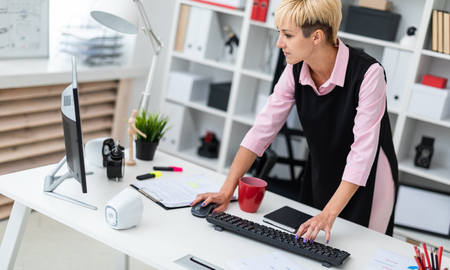 A young girl works in a bright office with documents and a computer. The girl has short white hair. Stock Photo