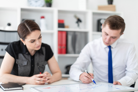Beautiful young girl and young man working in bright office. They have business attire. photo with depth of field