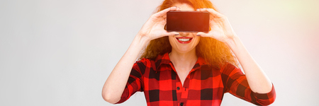 Portrait of attractive woman in checkered dress covering her eyes with mobile phone presenting it isolated on grey background with copyspace digital advertising concept.