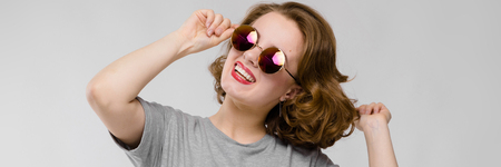 Beautiful young girl posing on gray background. Beautiful girl in round glasses dances
