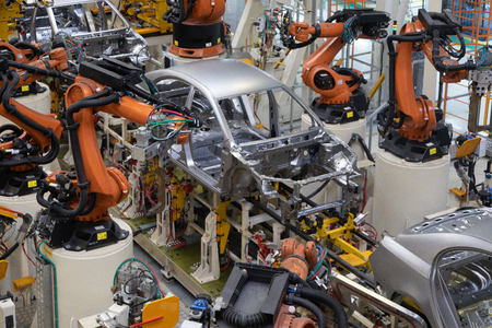 Tecnología moderna de montaje de automóviles. La planta de la industria automotriz. Tienda para la producción y montaje de máquinas vista superior. El proceso de soldadura de partes del automóvil.
