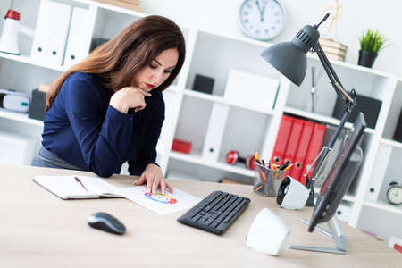 Charming girl working in a bright office. Girl dressed in blue sweater and dark trousers. She has long dark hair and beautiful makeup. photo with depth of field. Archivio Fotografico