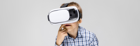 Portrait of a boy on a gray background. Boy in the glasses of virtual reality
