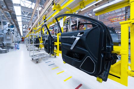 Preparación de puertas para instalación en fábrica de automóviles. Planta de producción y montaje de automóviles nuevos y modernos. Puerta de coche en línea de producción moderna Foto de archivo