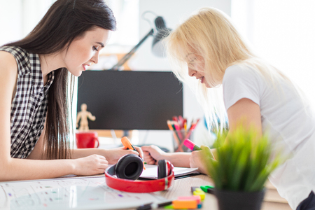 Two young beautiful girls work in a bright bright office. They are bent over the table and make notes with markers on the sheet. Girls have natural makeup and beautiful long hair. One of the girls is blonde, the other one has black hair. photo with depth of field Stockfoto